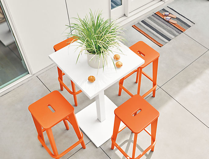 Detail of four Brook bar stools in orange on patio