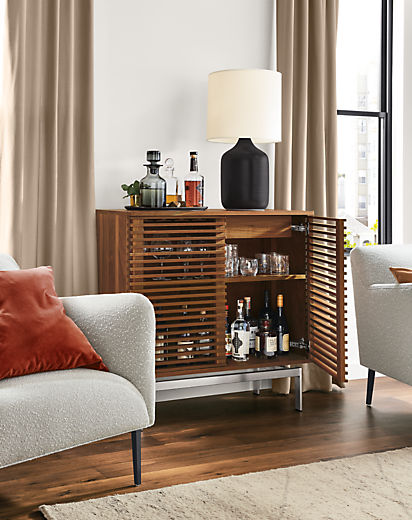 Detail of Coles two-door bar cabinet in walnut with stainless steel base in living room with right door open