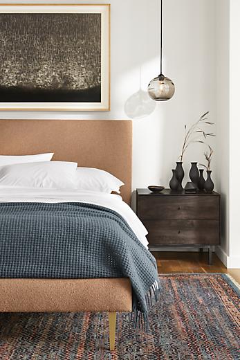 Close-up of Ella queen bed in Declan Sienna fabric beside Hudson nightstand