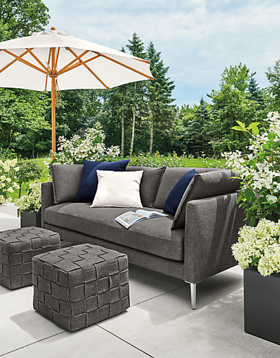 Detail of Palm sofa and Flet ottomans on patio with Cirro umbrella