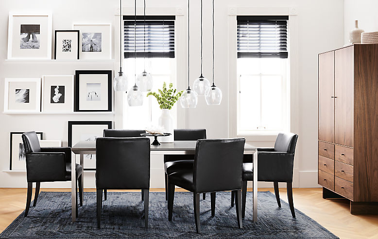 Detail of Portica dining table with stainless steel base and fog quartz top with black Marie chairs