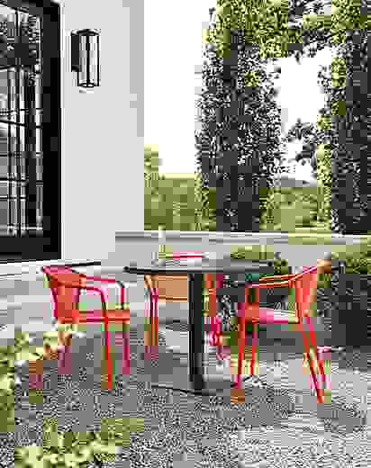 Detail of red Theo chairs and Maris round table on patio