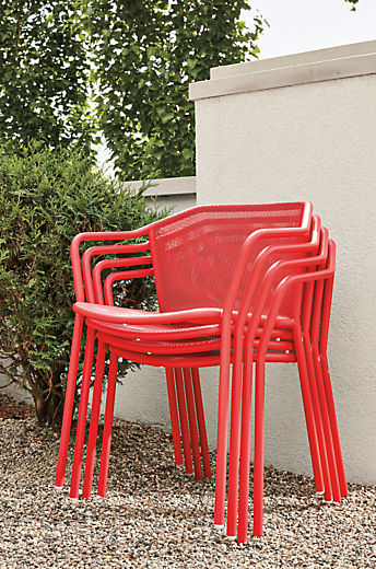 Detail of four red Theo chairs stacked outside