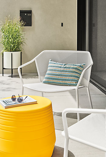 Detail of Theo outdoor lounge chair in white with Sunset pillow