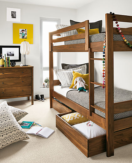 Detail of Waverly twin bunk in walnut in kids' bedroom with right trundle open